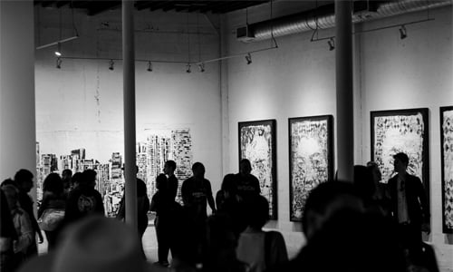 black and white photo of people in an art gallery
